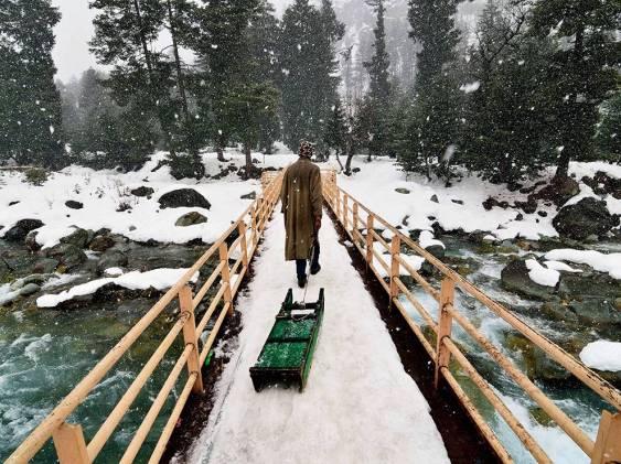 man-walking-snowy-bridge_89913_990x742